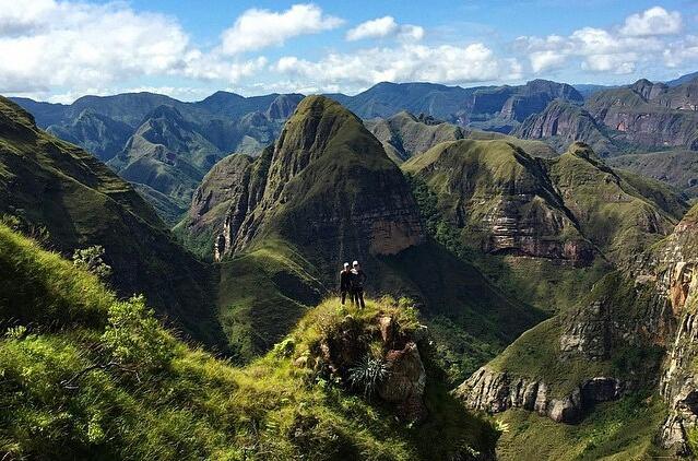Pareja en frente a paisaje montañoso y de vegetación