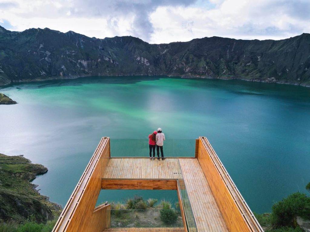 Pareja en un mirador observando laguna volcanica
