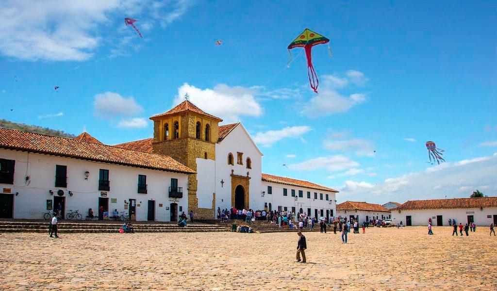 Iglesia y plaza con niños jugando con volantines en uno de los bellos lugares en colombia