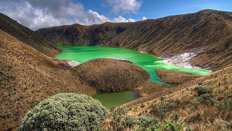 laguna color verde esmeralda enmedio de montañas