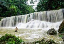 Hombre bajo gran cascada en la selva de pucallpa