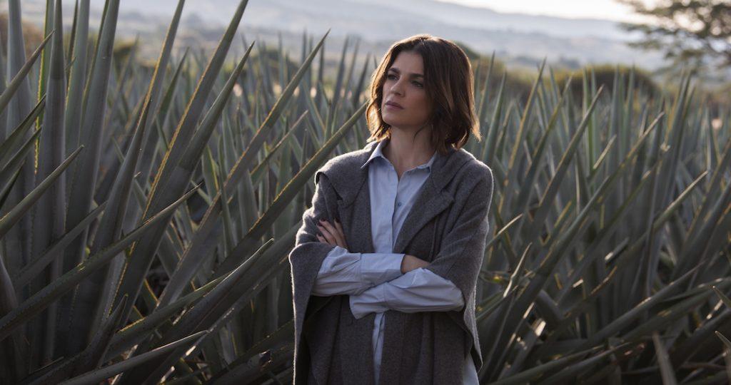 Mujer enmedio de plantaciones de tequila