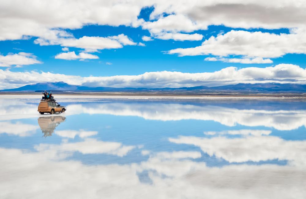 Auto enmedio de salar de uyuni inundado y reflejando el cielo