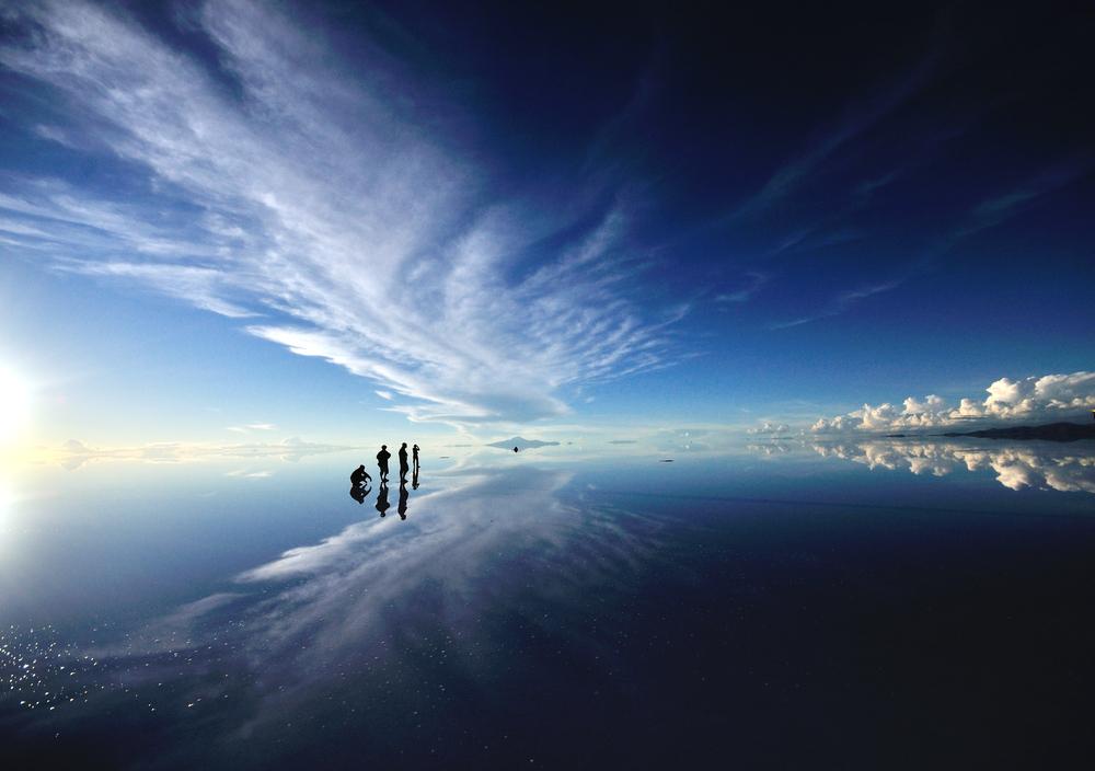 Viajeros parados en salar de uyuni durante efecto espejo