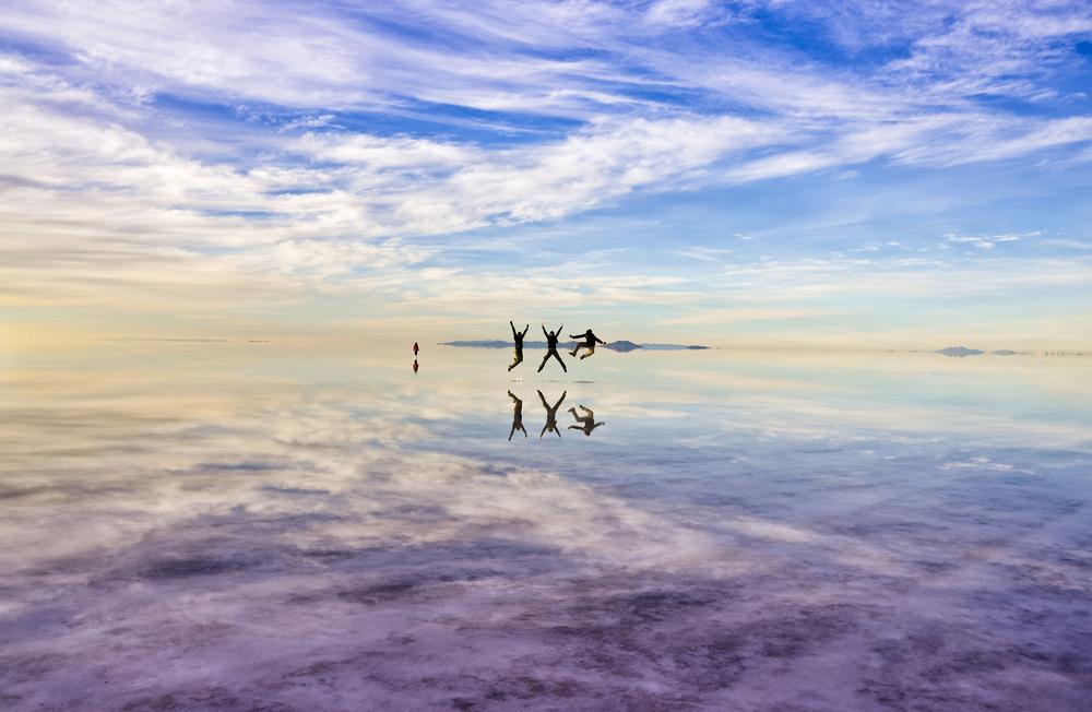 Viajeros en medio de salar de uyuni durante efecto espejo