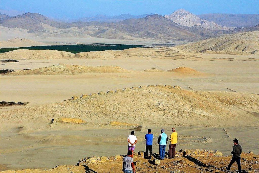 Personas observando restos arqueológicos en el desierto