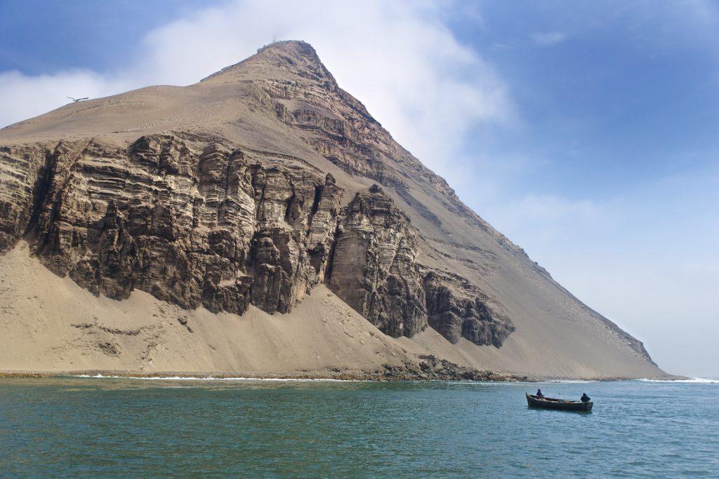 Barco frente a gran cerro en isla