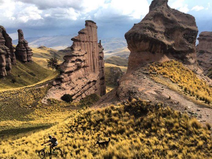 Ciclista bajando por ladera con formaciones rocosas espectaculares