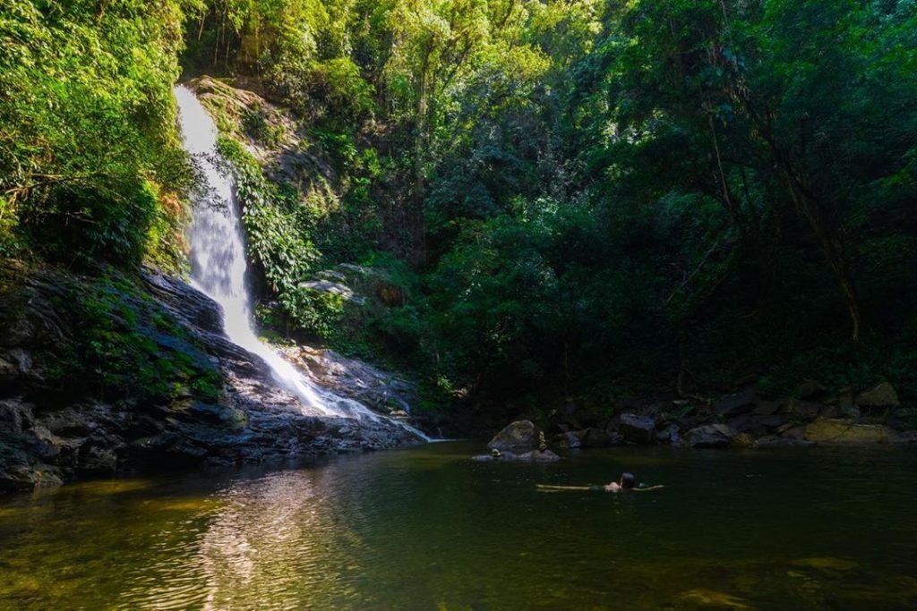 Catarata y persona bañandose en posa en la selva