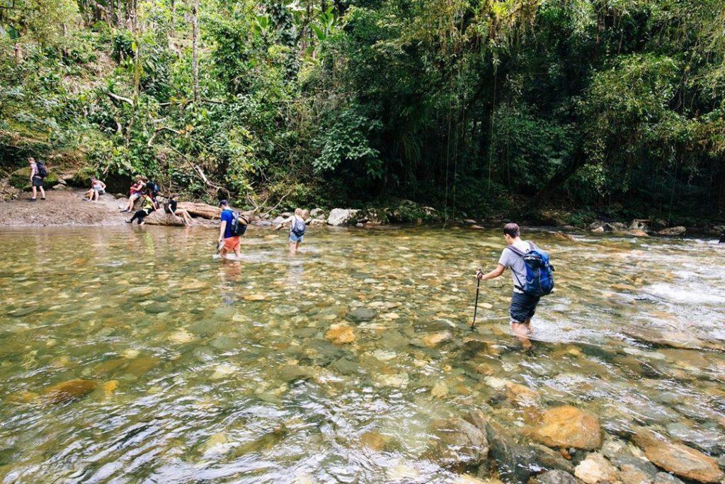 Viajeros cruzan un río en la selva colombiana