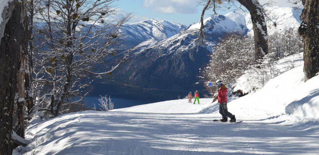 Snowboarder bajando por un cerro nevado en Bariloche