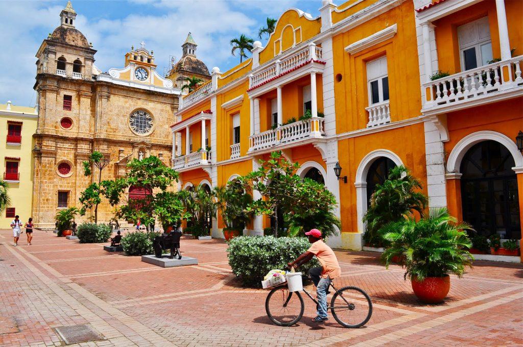 Joven andando en bicicleta por ciudad colonial en cartagena