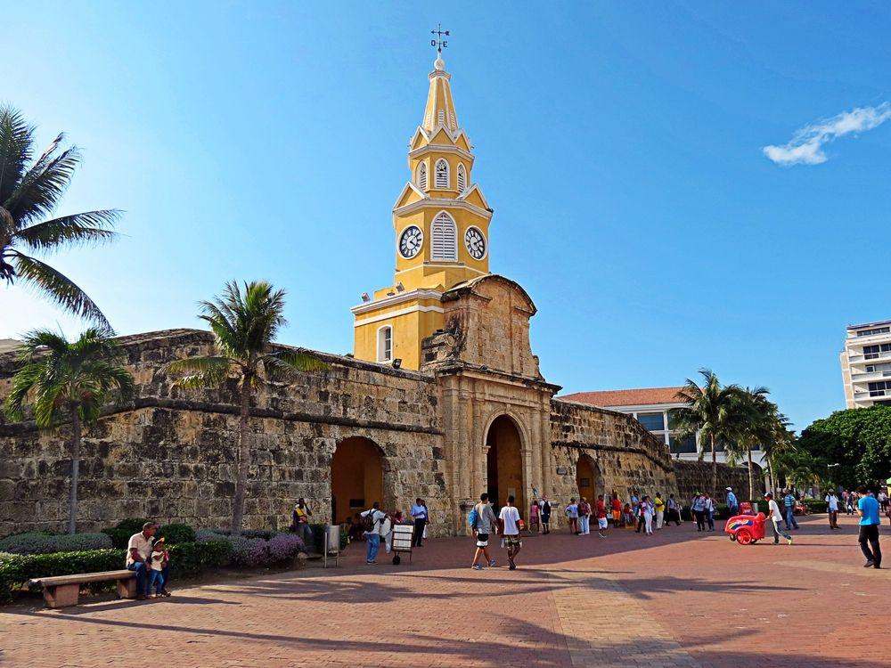 Personas caminando frente a torre del reloj en cartagena