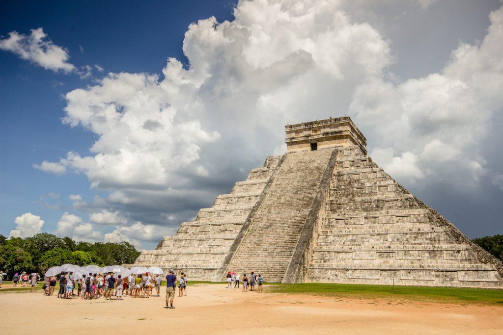 Grupo de viajeros bajo sombrilleros en CHichén Itzá