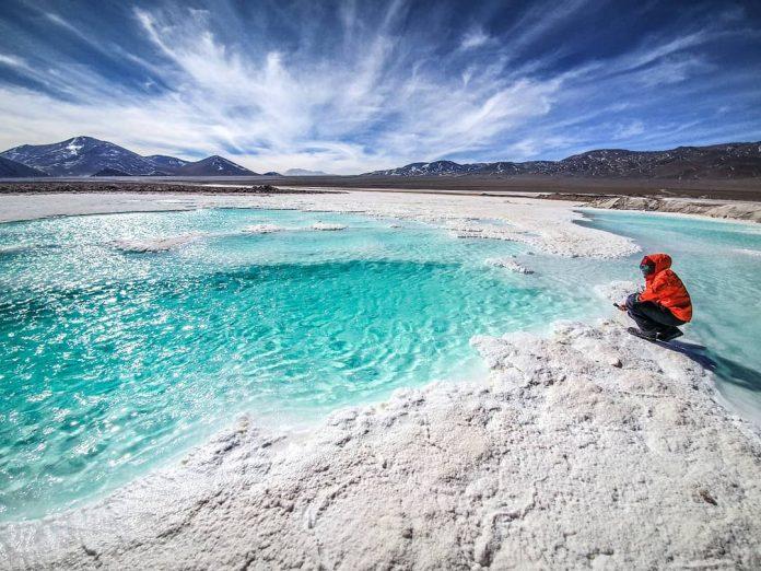 Viajero sentado frente a lagunas color turquesa