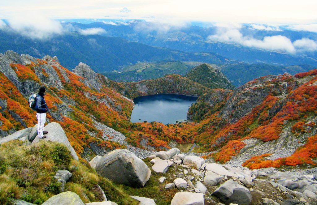 Viajero observando laguna desde una montaña