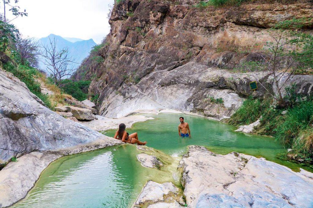 Dos viajeros bañándose en aguas color turquesa