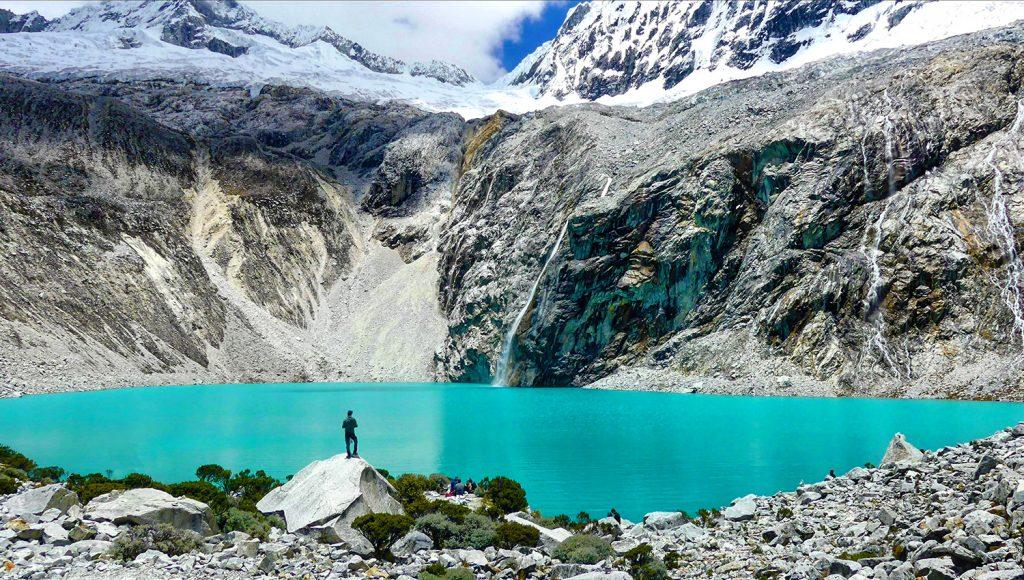 Viajero observando laguna color turquesa entre medio de montañas