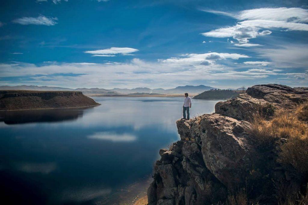 Persona observando lago desde las alturas