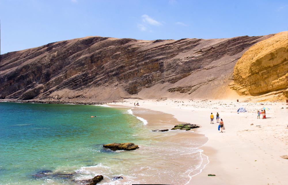 Personas caminando por una playa en el desierto del Perú