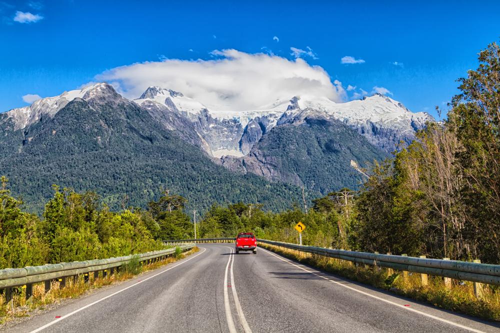 Auto rojo en carretera con montaña de fondo