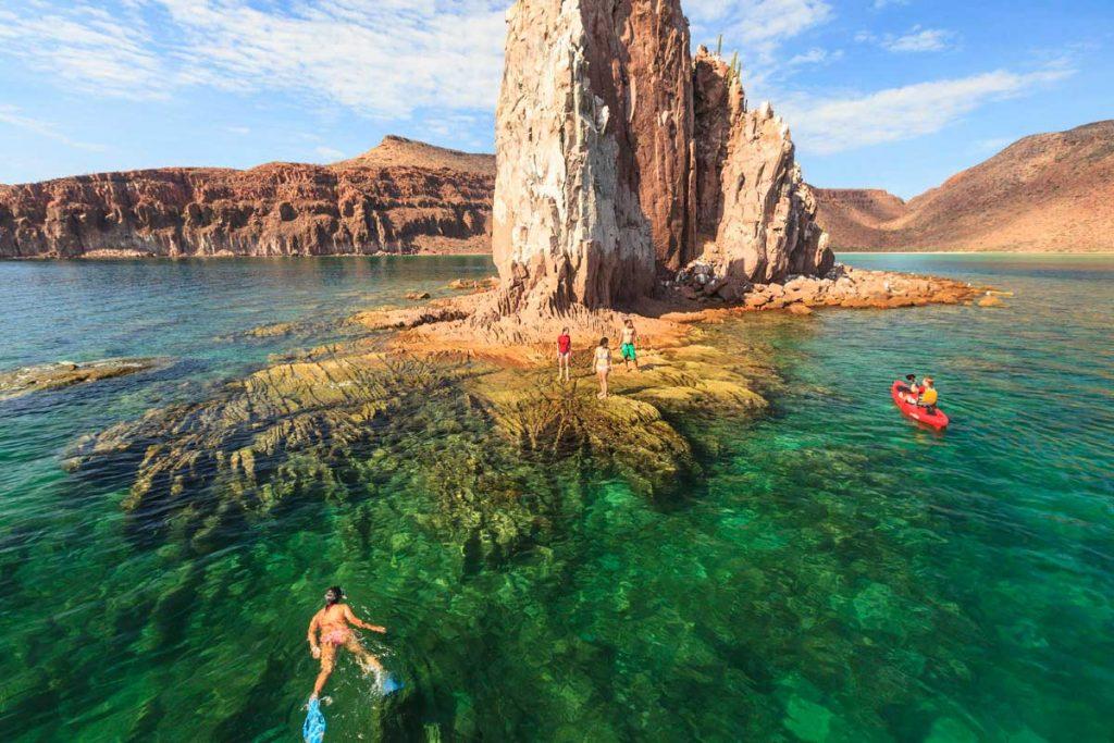 Personas nadando en el mar alrededor de gran roca