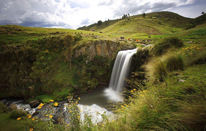 Cascada rodeada de amplio paisaje y leve vegetación