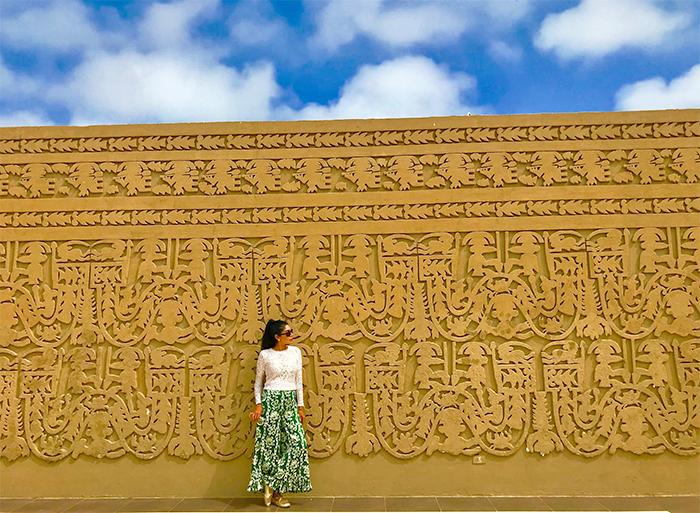 Mujer frente a muro de centro arqueológico en Trujillo