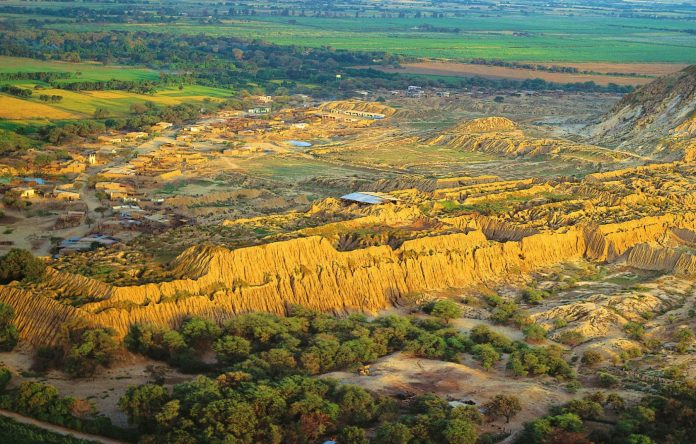 Pirámides de tierra en medio de paisaje con vegetación