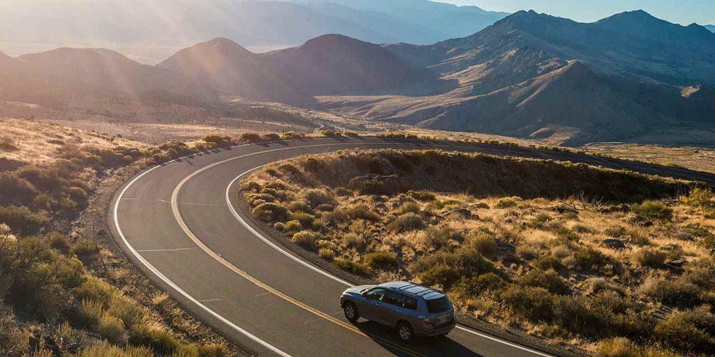 Carro viajando por la carretera y de fondo montañas