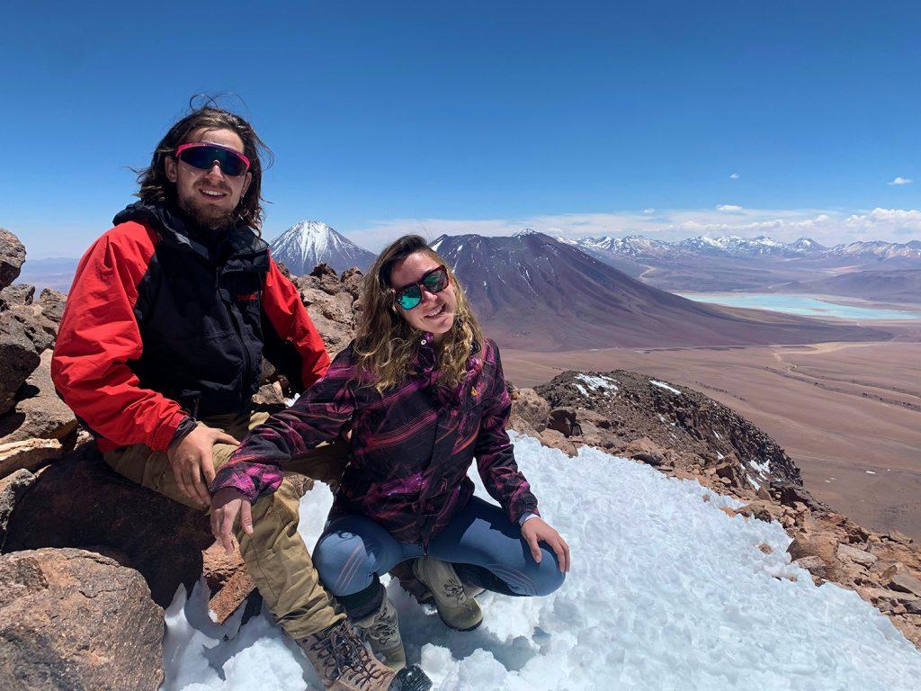 Pareja de viajeros en la cima de un volcán
