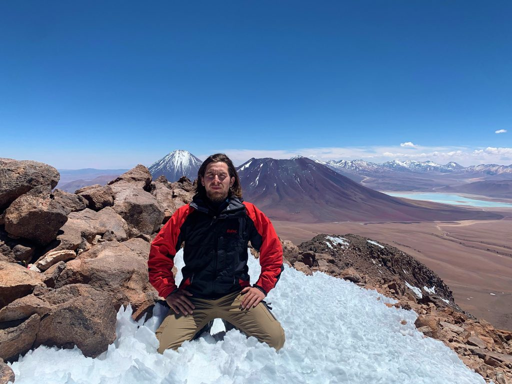 Hombre en la cima de volcan en el desierto