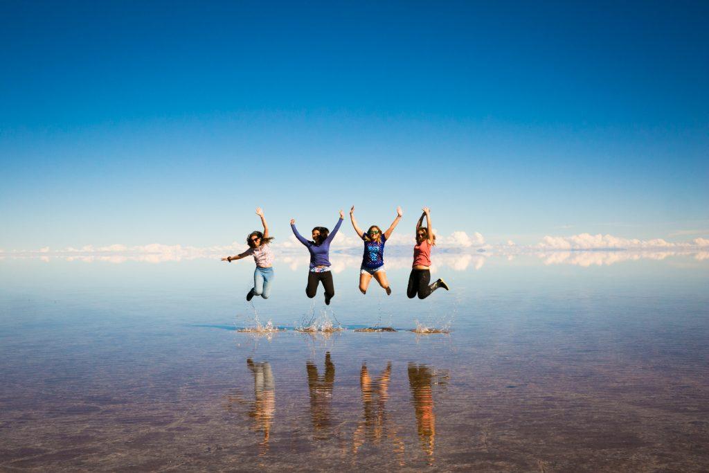 Viajeras en un salar que refleja el cielo