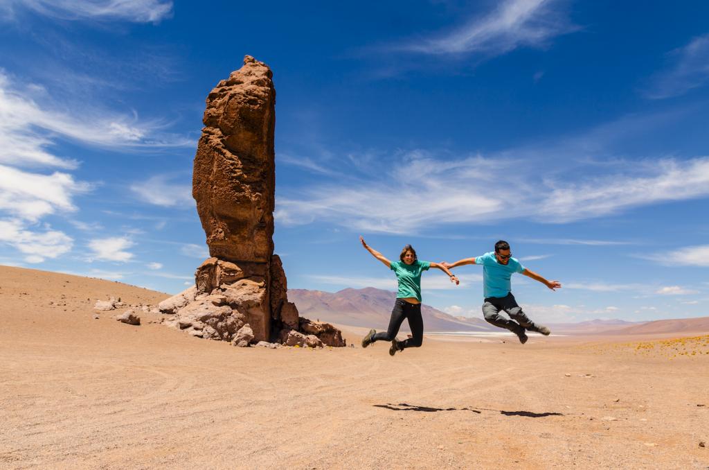 Dos viajeros saltando en medio del desierto