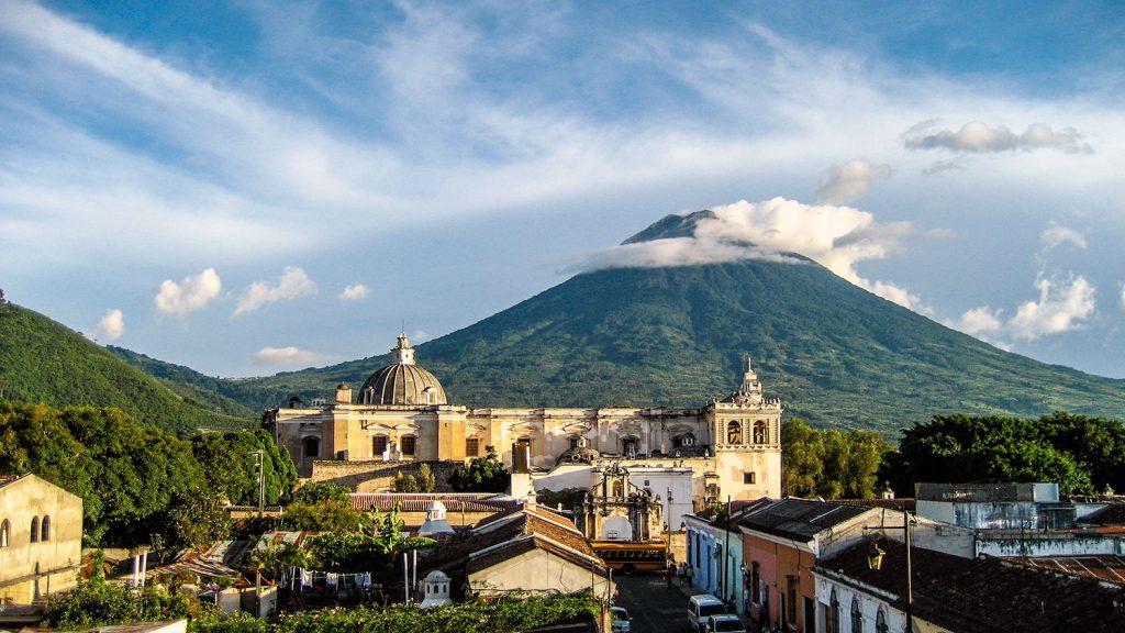 Ciudad colonial con gran volcan en el fondo