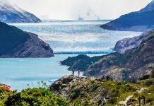 Glaciar de fondo entre las montañas y dos viajeros en torres del paine