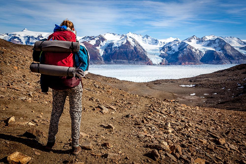 Persona observando glaciar y las montañas durante circuito w en torres del paine
