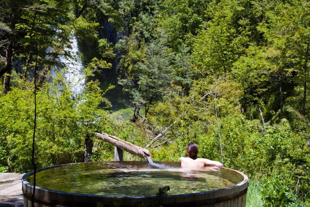 Persona bañandose en terma en medio del bosque de pucón