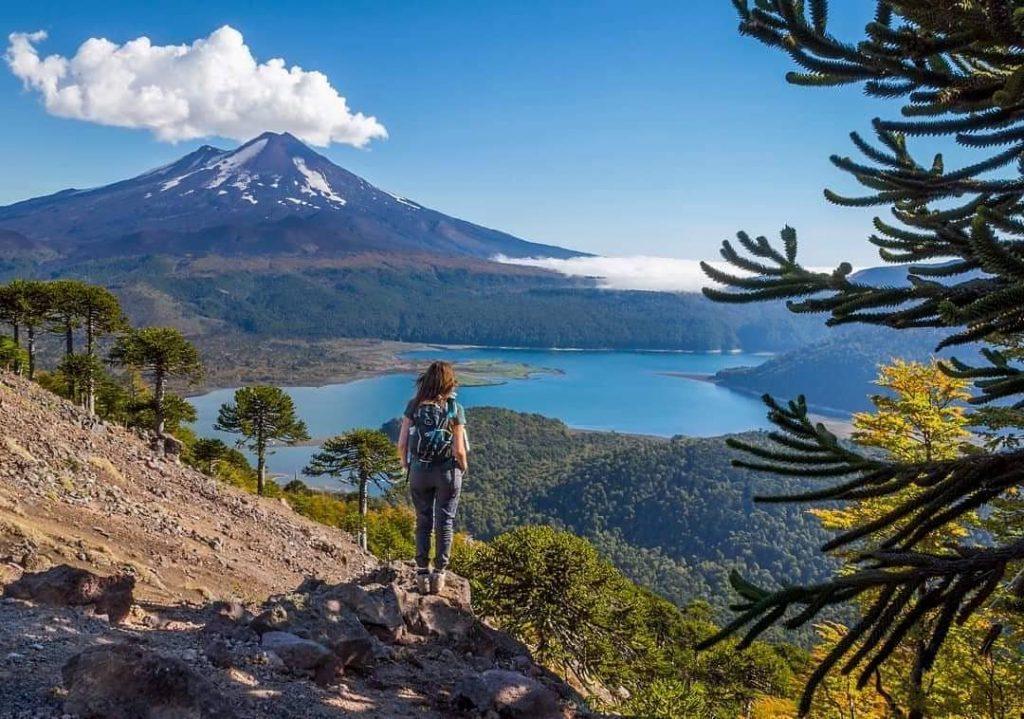Persona observando paisaje montañoso y lago desde mirador