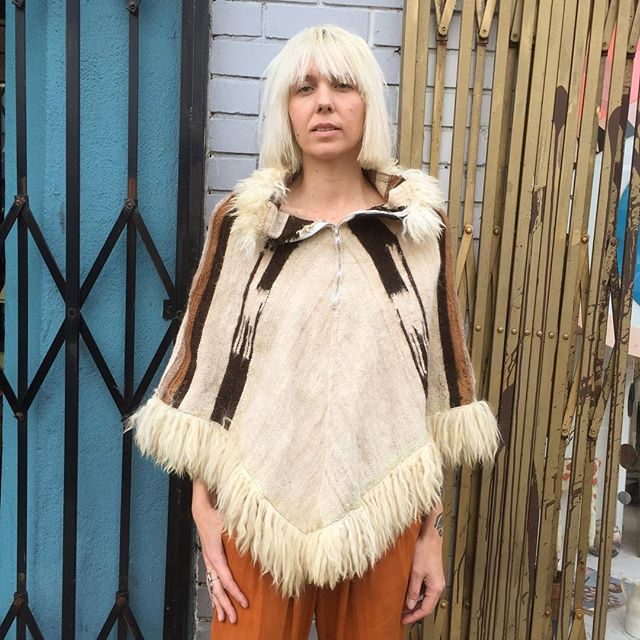 VACATION - It's always fun to invest in a statement piece!! This vintage 1970's wool alpaca poncho/cape is amazing!! The collar and trim are a Peruvian Llama fur!! There are llamas woven into the poncho!! The front has a zipper from the center to top (you can wear it a number of ways)!! There is a tiny part where the collar trim is cut, but it is not noticeable.  Fits S/M.