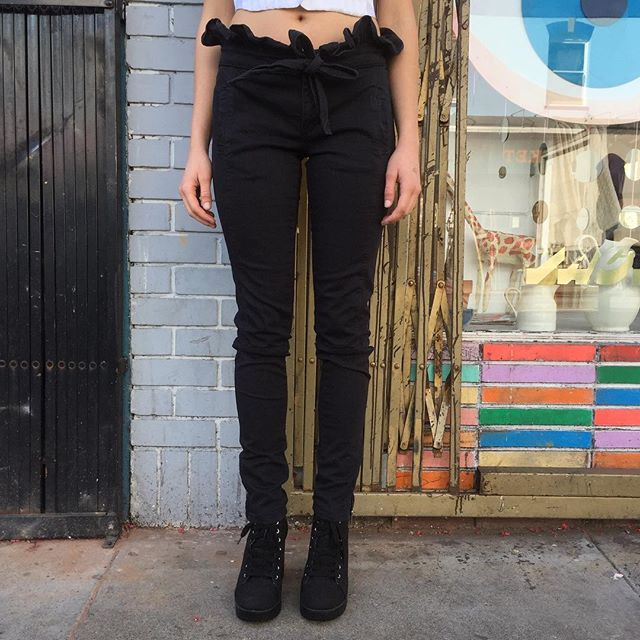 "VACATION - Mix Romanticism and tough urban street chic a pair of #VALENTINORED black skinny ruffle jeans.  The ruffle tie waistband is decidedly #VALENTINO infusing a touch of whimsy in black denim.  Pair with a white t-shirt or moto-jacket.  You'll look tres chick 🐥!! The cut is a mid rise skinny.  The leg has moto style seams with zippers at the ankle.  There are two small slit pockets in front.  No back pockets, but that would look weird on these jeans!! The waist measures 31"", rise 9"", and inseam 34""."