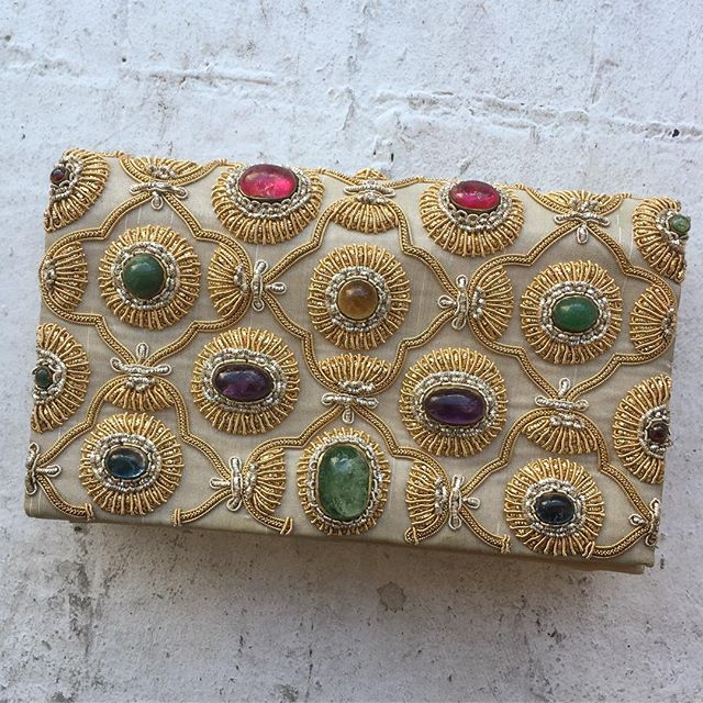 "VACATION - She and Richard Burton were denounced by the Vatican for ""erotic vagrancy"" after news broke of their relationship on the set of Cleopatra, when both were already married.  Liz Taylor, the lioness with purple eyes was iconic. This amazing jeweled clutch looks like a jem straight out of Liz's closet ✨✨. This clutch is timeless!! Pair it with a white t-shirt and jeans or a designer gown.  This clutch was made by Lewis.  Made in India.  The inside still has the original mirror in perfect condition.  There are three  pockets for your goodies and a removable coin purse 👛!! The outer is a gorgeous tan satin with Indian gold embroidery around multi colored baubles of beauty!! Measures 8""x6"". This bag is in great condition (there is a pen mark on the inside flap). The exterior is immaculate."
