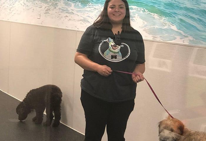 Canine Coach, Melanie, holding a Wheaten Terrier puppy on leash