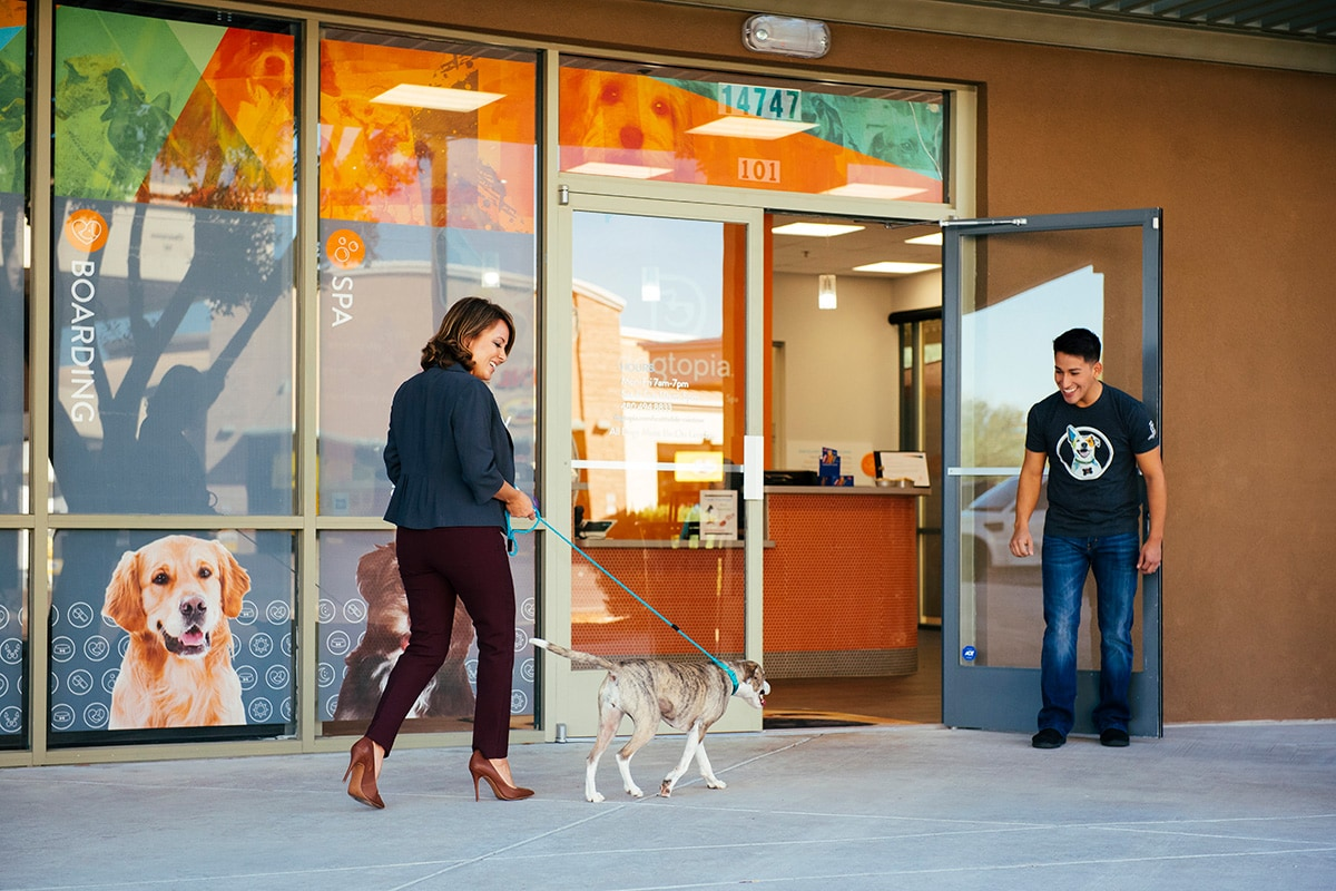 Woman coming into the Dogtopia center with her dog