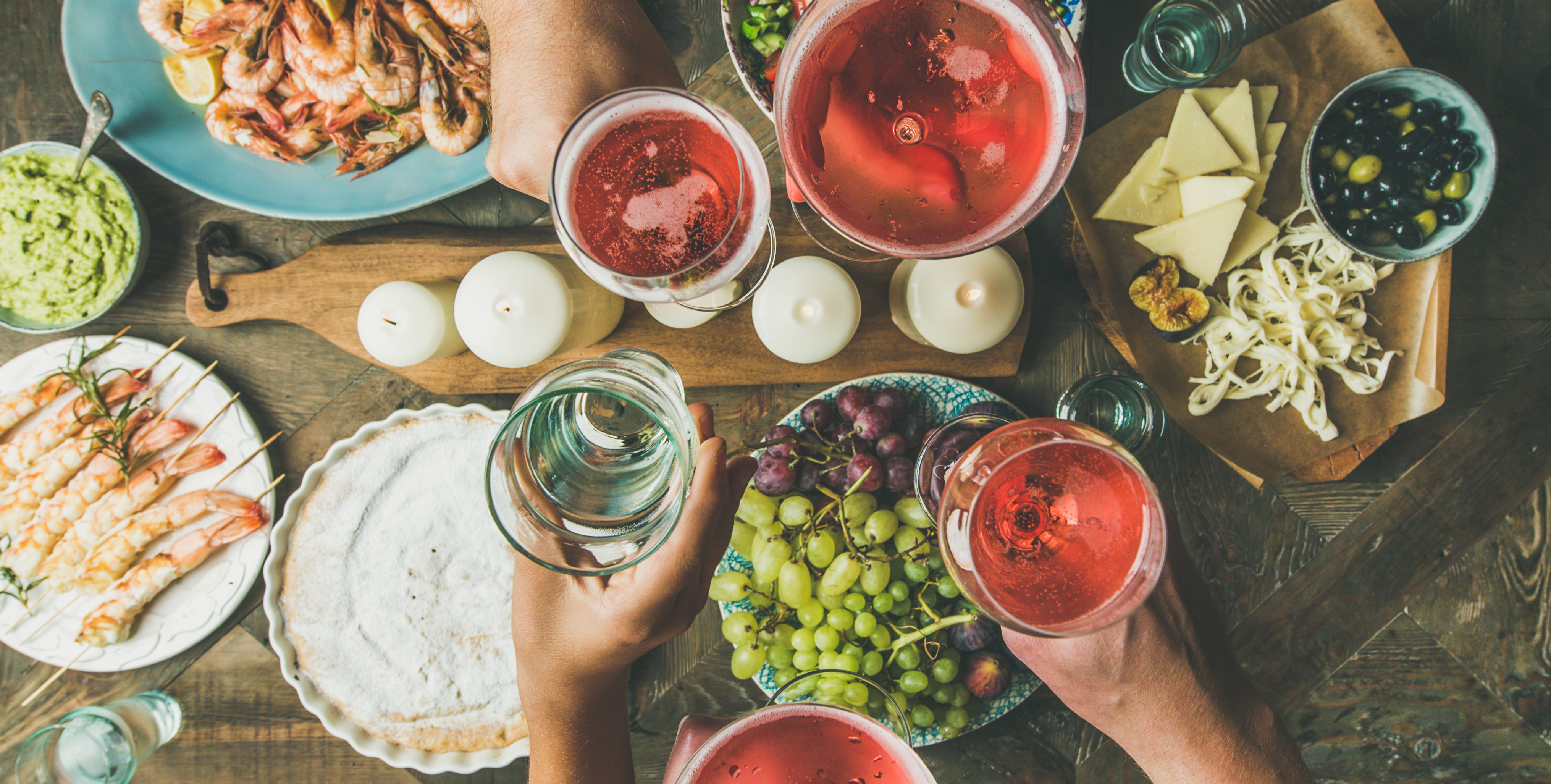 Holiday celebration table setting with food. Flat-lay of friends hands eating and drinking together. Top view of people having party, gathering, celebrating with rose champaign, wide composition