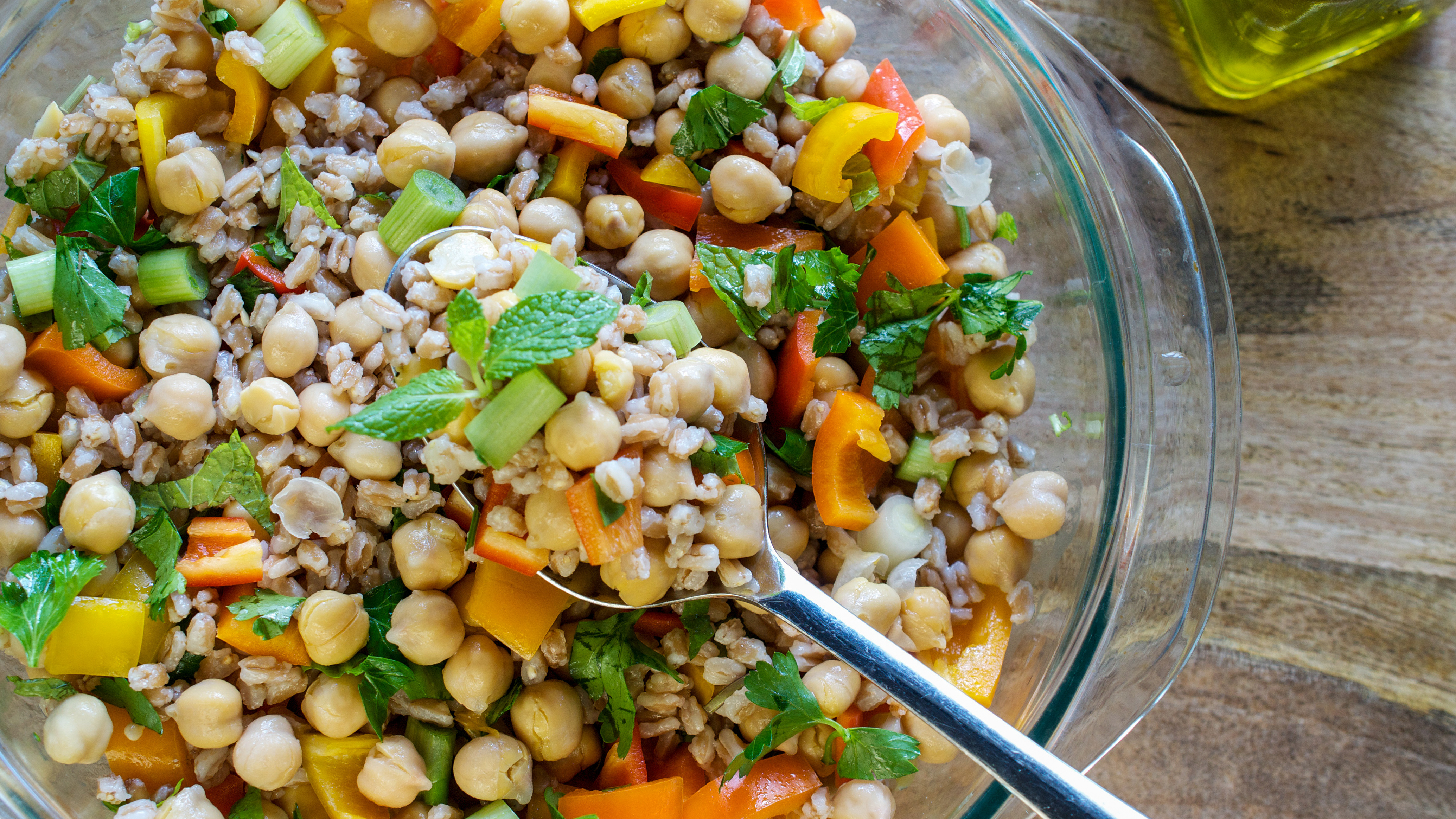 A salad consisting of farro, garbanzo beans, bell peppers, and spring onions served with olive oil on wooden table- healthy vegan eating concpet