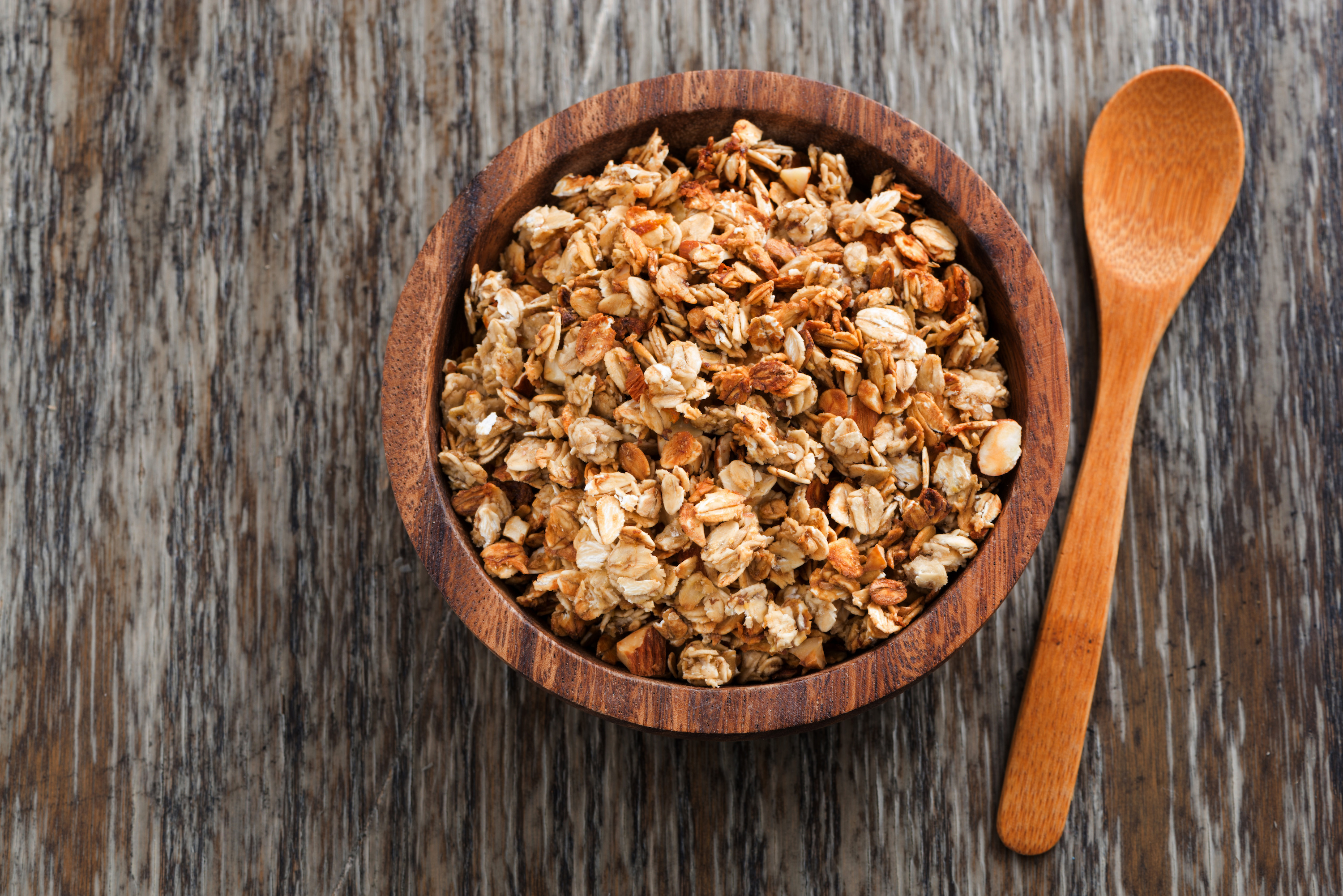 homemade granola in a wooden bowl and spoon, top view, close-up