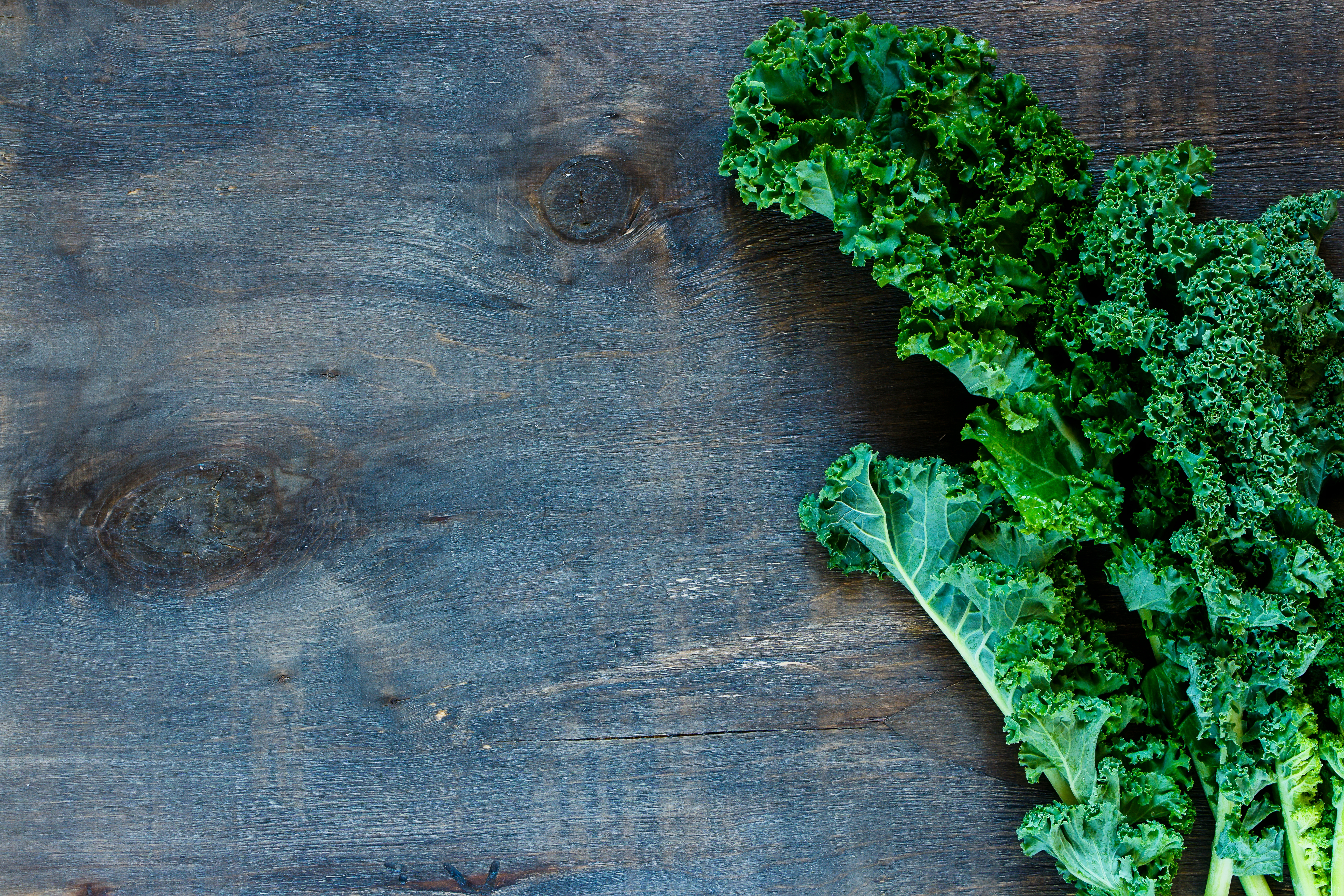 Top view of fresh green curly kale on rustic wooden background with space for text.