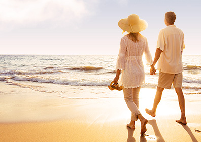 Man and Woman walking on the beach holding hands