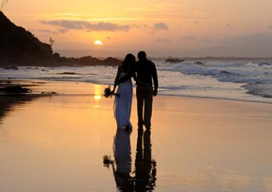 A couple standing on the beach in a wedding dress and suit